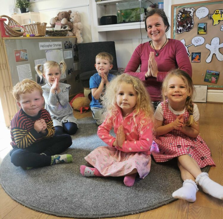 Townhouse pre-schoolers say Namaste with Everybody Yoga teacher Julie Welch